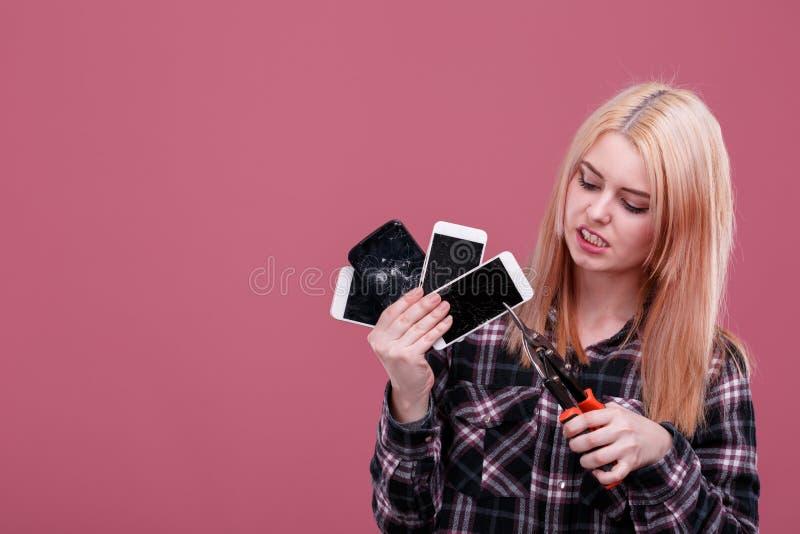 Une fille, prises plusieurs smartphones et les casse avec un fermoir Sur un fond rose photos stock
