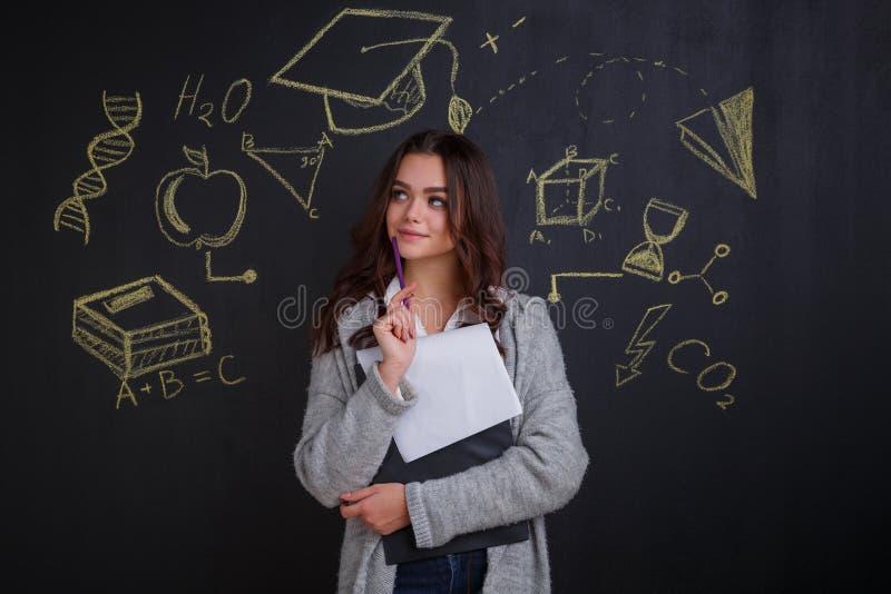 Une fille réfléchie tient un dossier avec des papiers dans des mains et recherche images libres de droits