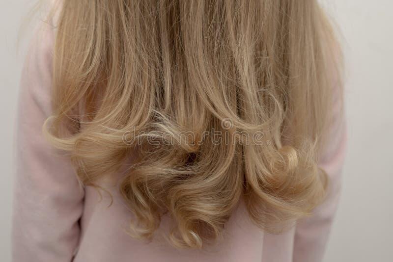 Une fille recule avec de beaux cheveux bouclés image libre de droits