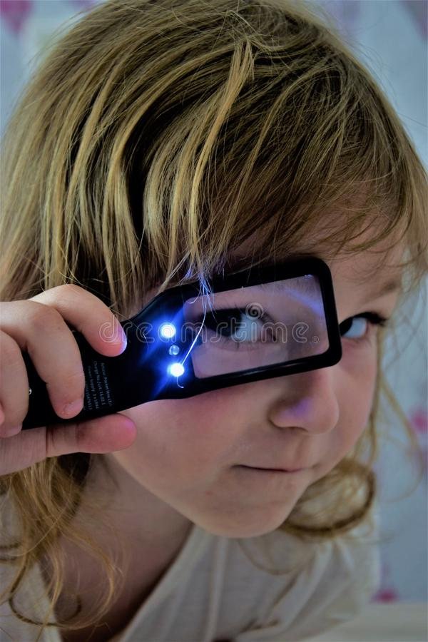 Une fille regardant par une loupe rétro-éclairée photo libre de droits