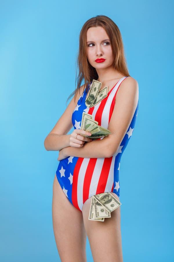 Une fille regarde avec les yeux sérieux au côté et tient un groupe de billets d'un dollar Un déjeuner sec dans une cuillère image libre de droits