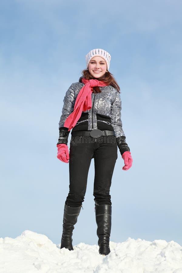 Une fille reste en hiver sur la neige et le sourire photographie stock libre de droits