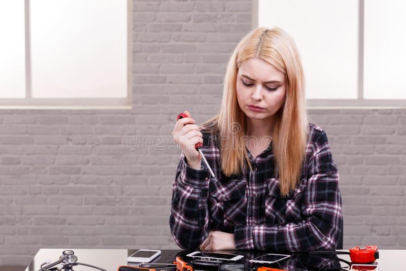 Une fille sérieuse et réfléchie, s'assied à côté d'un groupe de téléphones cassés et tient un tournevis indoors photographie stock libre de droits