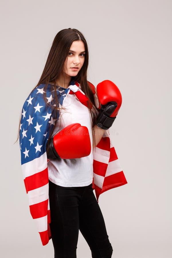 Une fille sérieuse, supports dans des gants de boxe et est couverte de drapeau américain photos stock