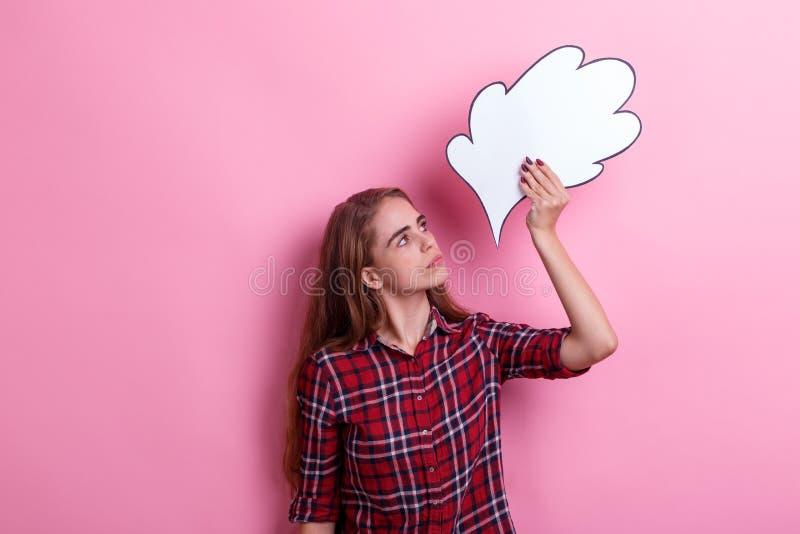 Une fille sérieuse tenant une image de pensée ou d'idée au-dessus de sa tête et la regardant Fond rose images stock