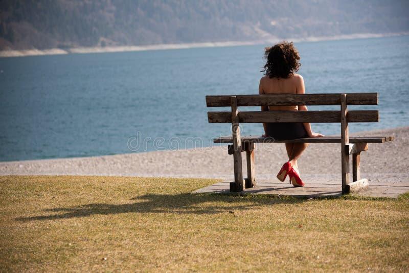 Une fille s'asseyant au-dessus de son épaule sur un banc en bois regarde un lac de montagne photo libre de droits