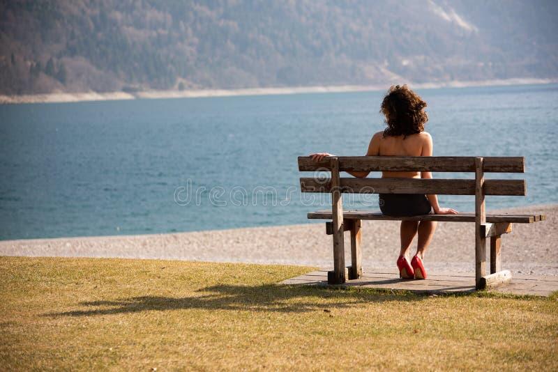 Une fille s'asseyant au-dessus de son épaule sur un banc en bois regarde un lac de montagne photos libres de droits