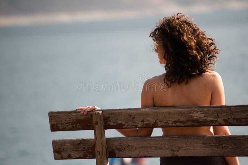 Une fille s'asseyant au-dessus de son épaule sur un banc en bois regarde un lac de montagne photographie stock libre de droits