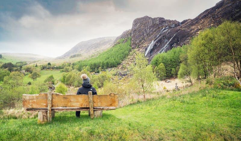 Une fille s'asseyant sur le banc en bois et regardant la cascade dans Kenmare photographie stock libre de droits