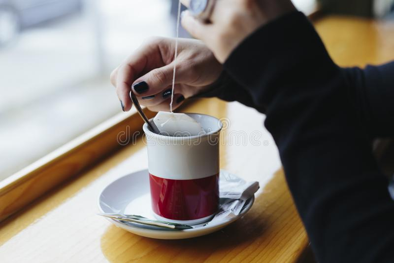 Une fille s'assied au siège fenêtre du café, buvant du thé image stock
