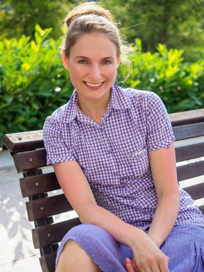 Une fille s'assied avec un sourire sur un banc en parc d'été image stock