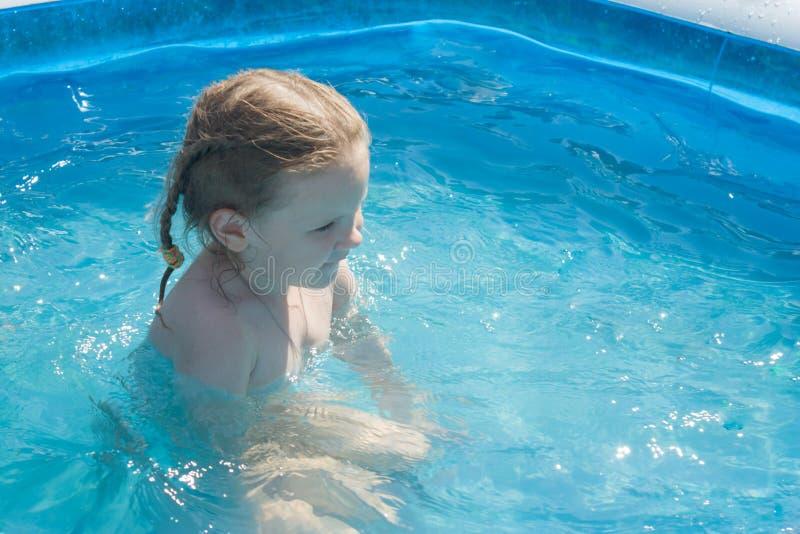 Une fille s'assied dans l'eau d'une piscine gonflable image stock
