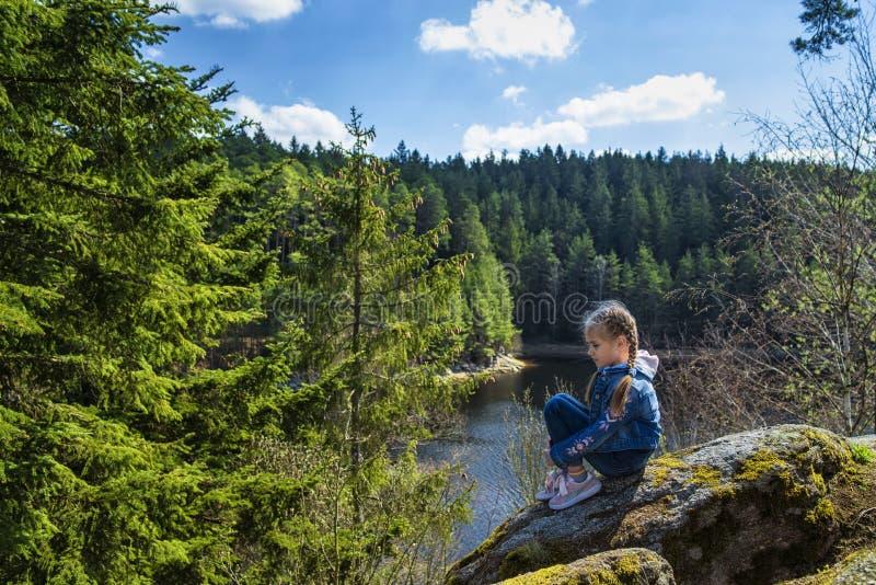 Une fille s'assied sur une falaise et des regards ? la nature, fille s'asseyant sur une roche et appr?ciant la vue de vall?e photos stock