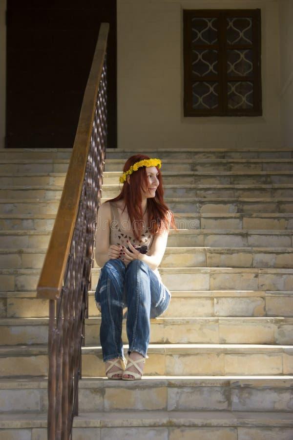 Une fille s'assied sur les escaliers et regarde la fenêtre image libre de droits
