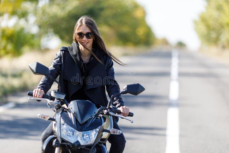 Une fille s'assied sur une moto dans des vêtements en cuir noirs photos stock
