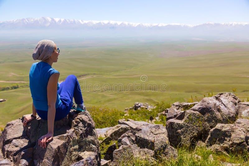 Une fille s'assied sur une roche sur un fond d'un paysage de ressort de montagne images libres de droits