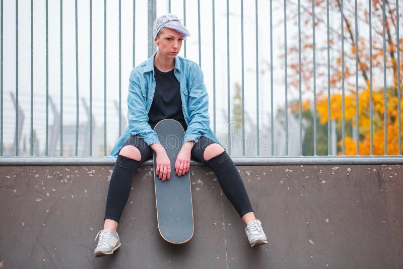 Une fille s'assied sur un overclock avec un patin dans sa main photos stock