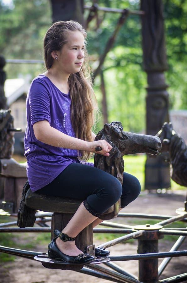 Une fille se débarrassant sur un cheval en bois photographie stock libre de droits