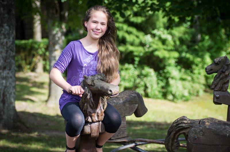 Une fille se débarrassant sur un cheval en bois photo stock