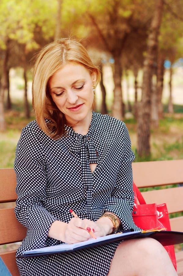 Une fille se reposant en parc, à l'heure du déjeuner Une femme dans l'amour La femme pense quoi écrire image libre de droits