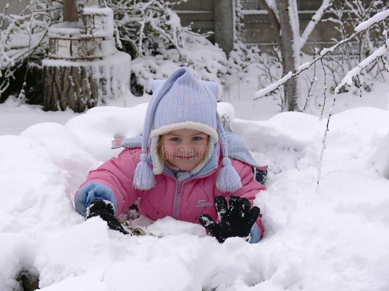 Une fille se situant dans la neige image stock