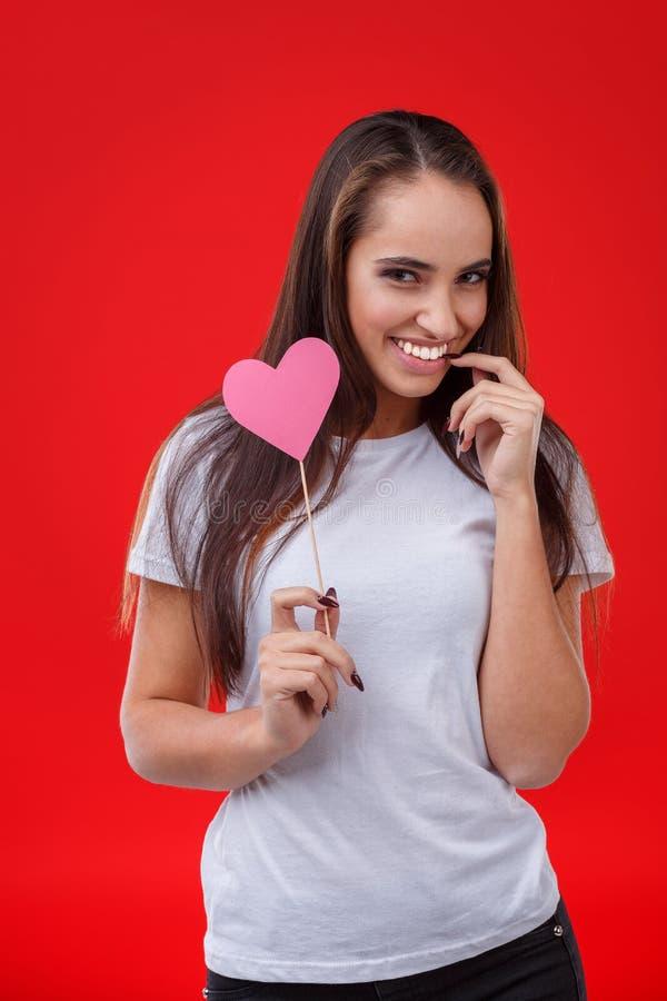 Une fille se tient avec un regard gêné et tient un coeur de papier rose sur un bâton et un sourire Fond rouge photos stock
