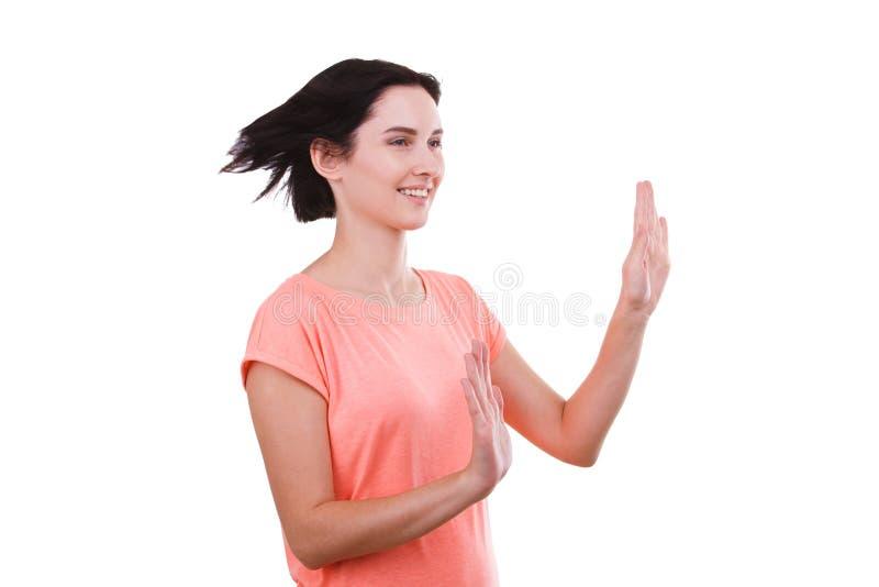 Une fille se tient moitié-tournée et tient ses paumes devant elle sur un fond blanc image libre de droits