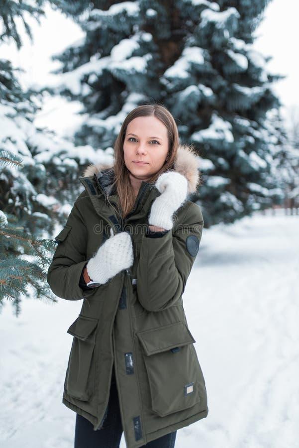 Une fille se tient pendant l'hiver sur le fond des arbres couverts de neige dans la forêt dans une veste chaude et des mitaines b photos stock