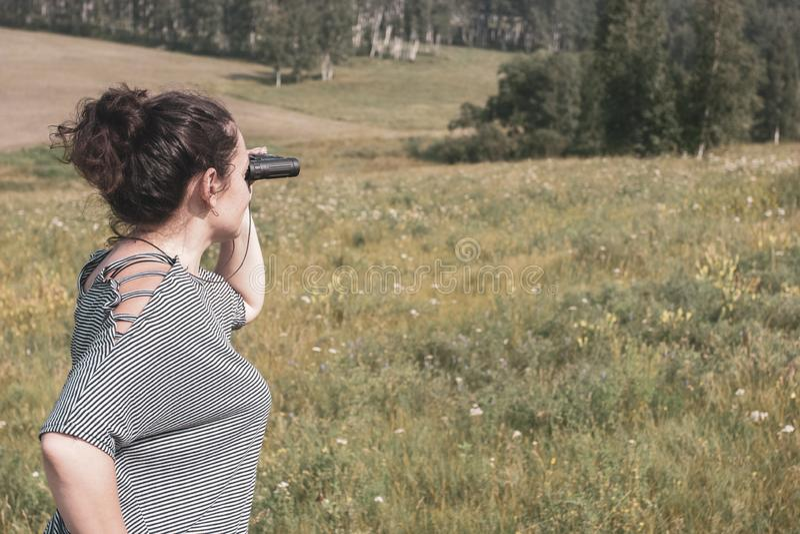 Une fille se tient sur le champ et les regards vers la forêt avec des jumelles photographie stock