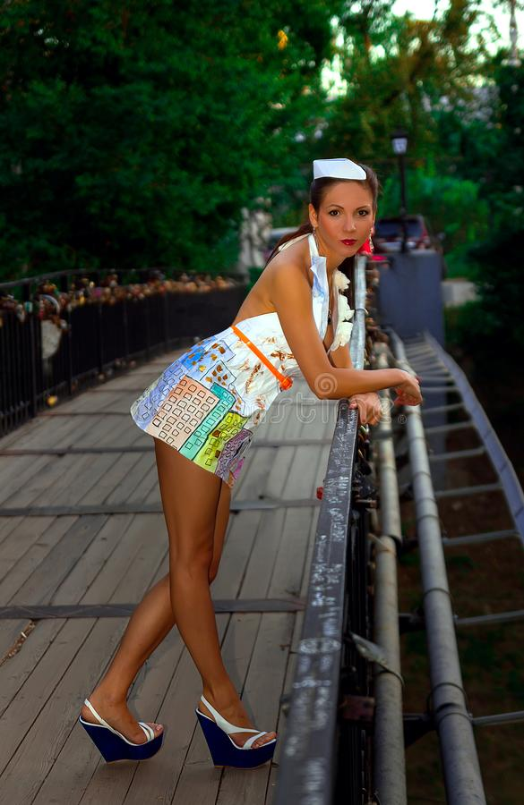 Une fille sexy sérieuse se tient sur le pont se penchent pour lui dans une robe de papier à la mode regardant la caméra photos stock