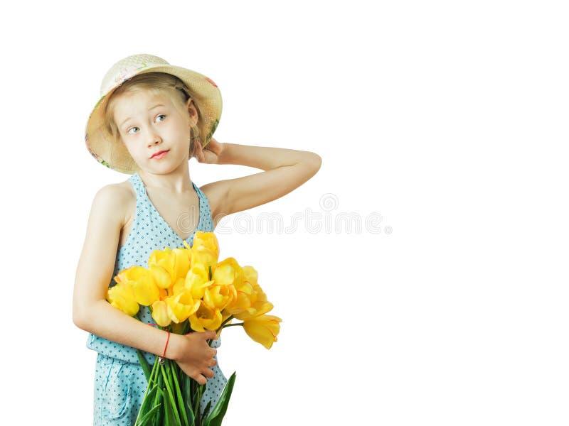 Une fille songeuse avec un chapeau et un bouquet des tulipes d'isolement sur le fond blanc photo libre de droits