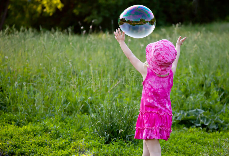 Une fille souffle des bulles images stock