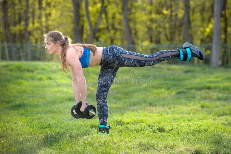 Une fille sportive sur un toit de char bleu avec des haltères noires dans les mains fait un exercice sur fond de nature estivale photographie stock