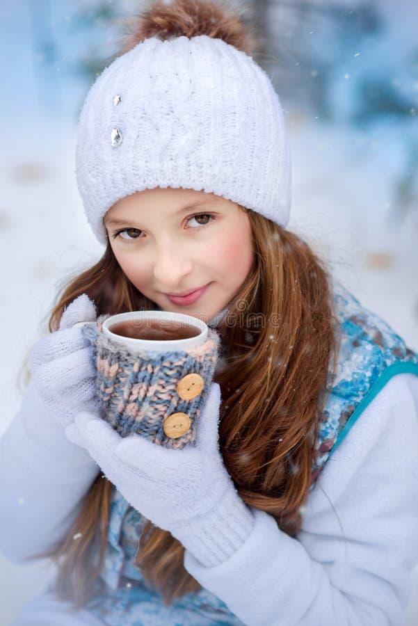 Une fille sur la promenade en parc couvert de neige d'hiver photographie stock libre de droits