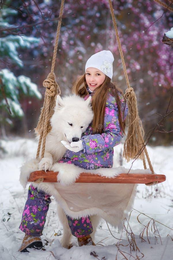 Une fille sur la promenade en parc couvert de neige d'hiver photos stock