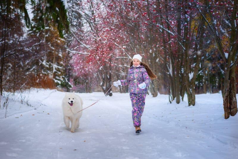 Une fille sur la promenade en parc couvert de neige d'hiver photo stock