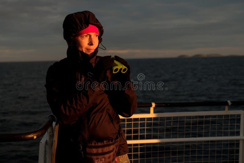 Une fille sur un bateau regarde par des jumelles le coucher du soleil photographie stock libre de droits