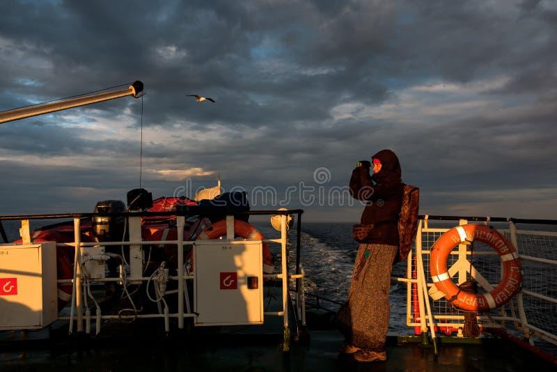 Une fille sur un bateau regarde par des jumelles le coucher du soleil images libres de droits
