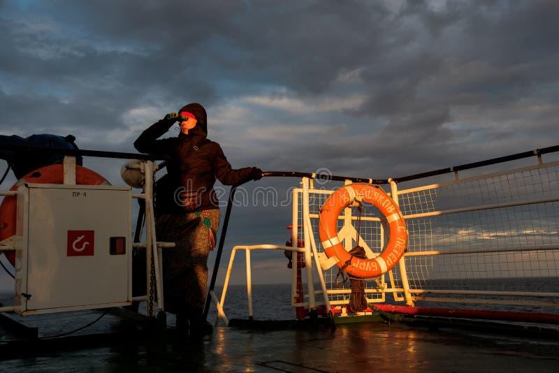 Une fille sur un bateau regarde par des jumelles le coucher du soleil images stock