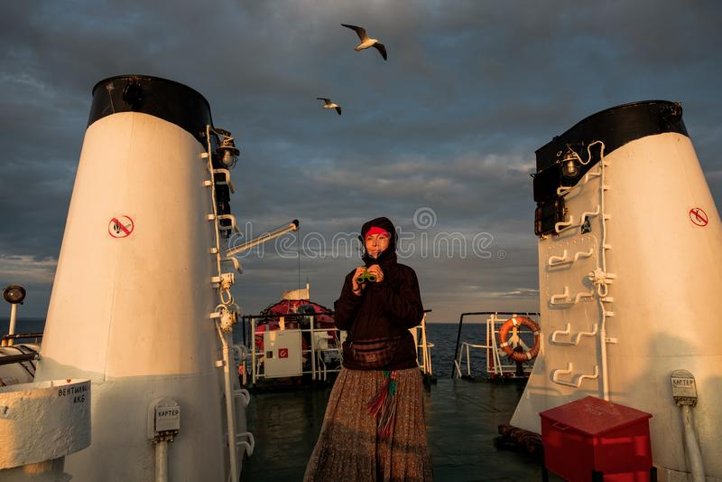 Une fille sur un bateau regarde par des jumelles le coucher du soleil photos libres de droits