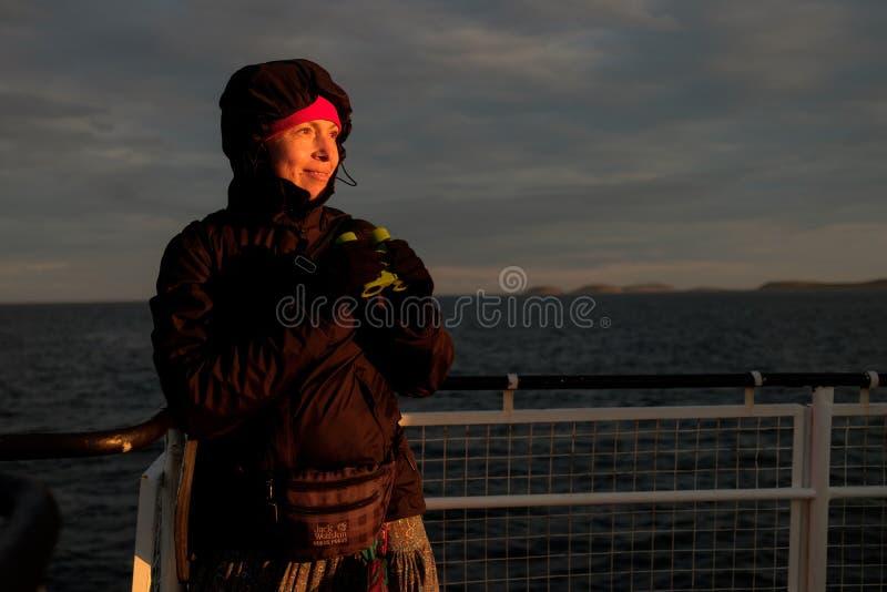 Une fille sur un bateau regarde par des jumelles le coucher du soleil photo stock