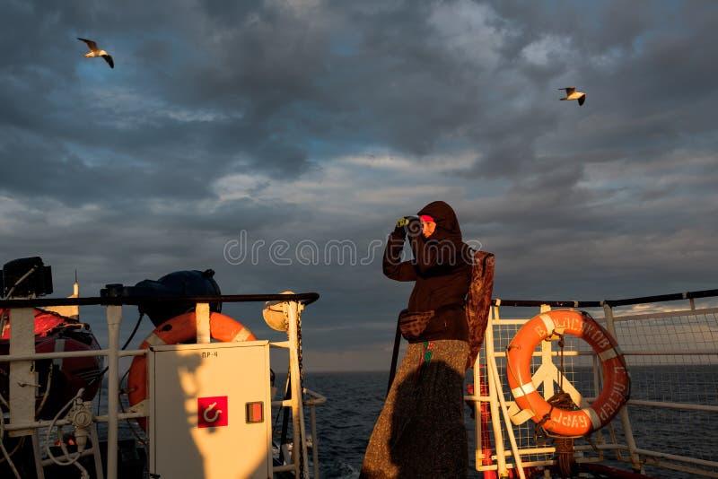 Une fille sur un bateau regarde par des jumelles le coucher du soleil photo libre de droits