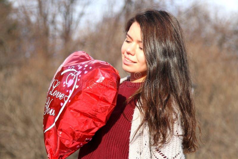Une fille tenant un ballon sous forme de coeur image libre de droits