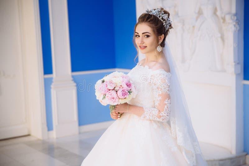 Une fille tendre avec les boucles lumineuses dans une robe du ` s de jeune mariée tient un bouquet des pivoines dans un hall bleu images libres de droits