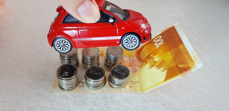 Une fille tient le petit jouet rouge de Fiat 500 dans la sa remettent 100 shekels israéliens photo libre de droits