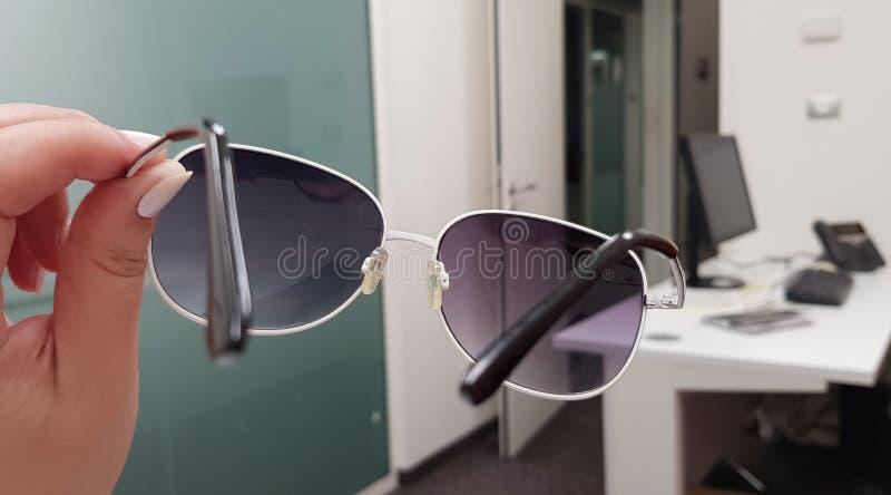 Une fille tient les lunettes de soleil à la mode dans sa main et les voit une salle vide de bureau photo libre de droits