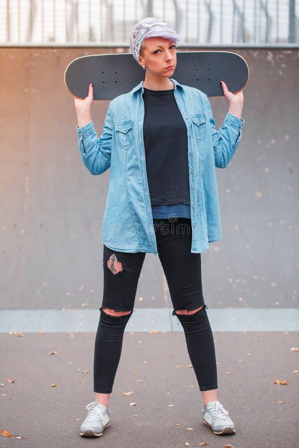 Une fille tient une planche à roulettes derrière ses épaules en parc de patin photographie stock libre de droits
