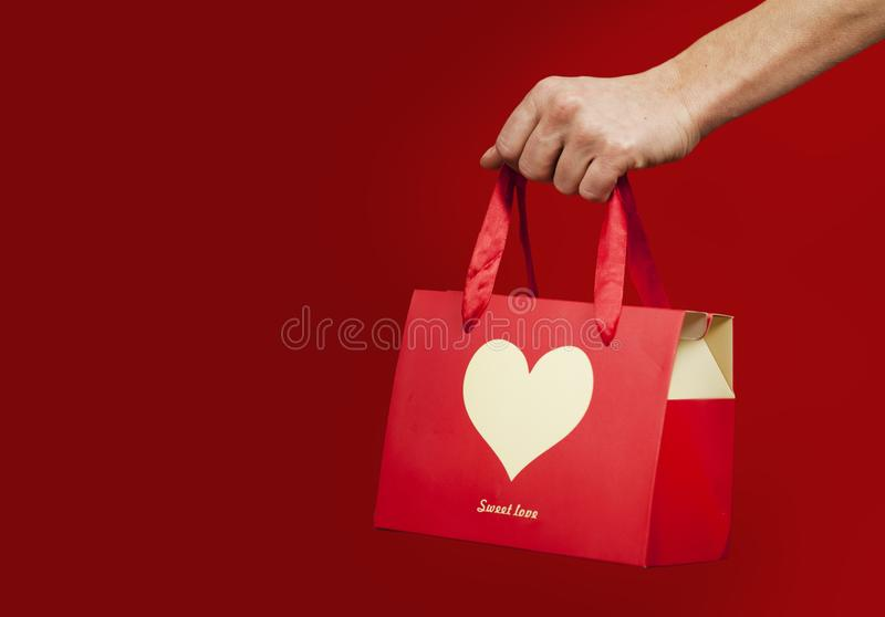 Une fille tient un cadeau avec un plan rapproché de coeur sur un fond rouge d'isolement Concept de Saint Valentin photo stock