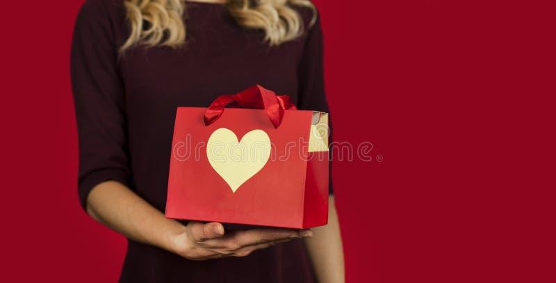 Une fille tient un cadeau avec un plan rapproché de coeur sur un fond rouge d'isolement Concept de Saint Valentin photos stock