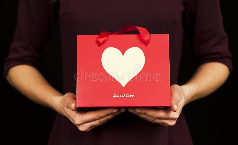 Une fille tient un cadeau avec un plan rapproché de coeur sur un fond rouge d'isolement Concept de Saint Valentin image stock